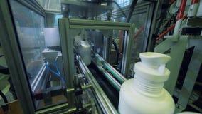 Vita flaskor med kemikalien som på flyttar en fabrikstransportör, automatiserad produktion arkivfilmer