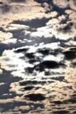Vita fluffiga moln för stackmoln silhouetted mot solen och den djupblå himlen royaltyfri bild