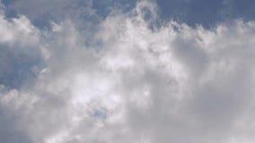 Vita fluffiga moln som rullar över en blå himmel arkivfilmer