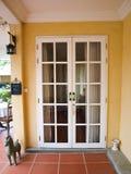 Vita franska dörrar för dubbel uteplats med fönster på den gula väggen Arkivfoton