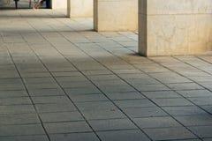 Vita fyrkantiga kolonner i en stad parkerar royaltyfria foton