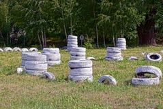 Vita gamla gummihjul på ett sportfält i gräset Arkivfoto