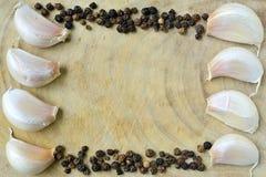 Vita garlics och svartpeppar. Arkivbild