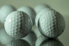 Vita golfbollar som reflekterar på en platta av exponeringsglas royaltyfri foto