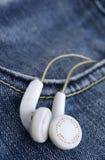 Vita hörlurar i denimjeansfack Fotografering för Bildbyråer