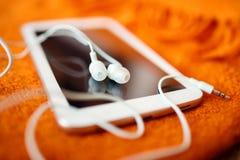 Vita hörlurar och minnestavlaPC Arkivbild