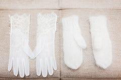 Vita handskar och tumvanten på Gray Textile Royaltyfria Foton