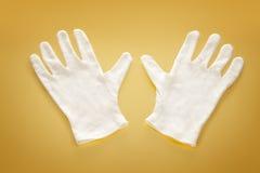 Vita handskar på gul bakgrund Arkivbild