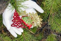 Vita handskar som rymmer julpynt Royaltyfri Fotografi
