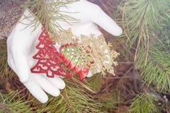 Vita handskar som rymmer julpynt Royaltyfri Bild