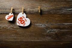 Vita hjärtor och rabatter med den romantiska modellen på träbakgrund Hjärtor av femtio procent royaltyfri foto
