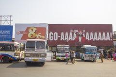Vita indiska bussar står i rad på bussstationen på bakgrunden av affischtavlor och folk arkivfoton