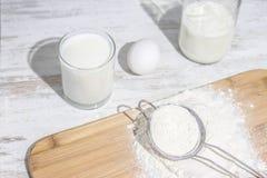 Vita ingredienser på köket: mjölka i exponeringsglas, ägg och mjöl med långa skuggor Fotografering för Bildbyråer