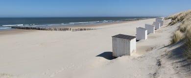 Vita kabiner på en solig strand Arkivbilder