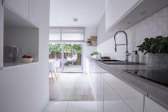 Vita kabinetter i ljus modern kökinre av huset med terrassen Verkligt foto