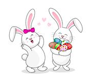 Vita kaniner för gullig tecknad film som rymmer påskägg royaltyfri illustrationer