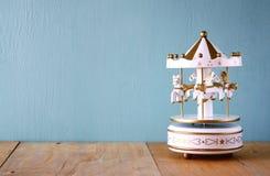 Vita karusellhästar för gammal tappning på trätabellen retro filtrerad bild Arkivbilder