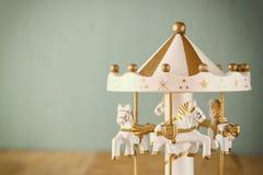 Vita karusellhästar för gammal tappning på trätabellen retro filtrerad bild Royaltyfri Bild