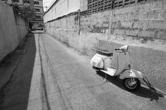 Vita klassiska sparkcykelställningar som parkeras nära den konkreta gamla väggen, w Arkivfoton