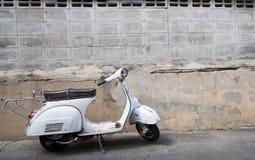 Vita klassiska Vespasparkcykelställningar som parkeras nära den gamla betongen Royaltyfri Bild