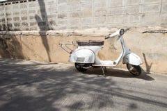 Vita klassiska Vespasparkcykelställningar som parkeras nära den gamla betongen Royaltyfria Foton