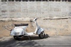 Vita klassiska Vespasparkcykelställningar som parkeras nära den gamla betongen Arkivfoton
