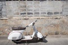 Vita klassiska Vespasparkcykelställningar som parkeras nära den gamla betongen Royaltyfri Foto