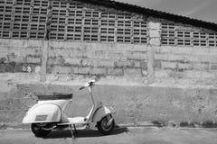 Vita klassiska Vespasparkcykelställningar som parkeras nära den gamla betongen Arkivbild