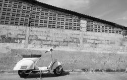Vita klassiska Vespasparkcykelställningar som parkeras nära den gamla betongen Fotografering för Bildbyråer