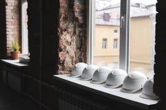 Vita konstruktionshjälmar ligger på fönsterbrädan i rad inom byggnaden under konstruktion Royaltyfri Bild