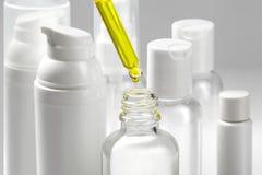 Vita kosmetiska flaskor med brunnsortskönhetsmedelolja Wellnessen, brunnsorten och kroppen att bry sig flasksamlingen olja för ba Royaltyfri Bild