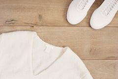 Vita kvinnor tröja och gymnastikskor på vit päls mattar, träbakgrund Lägenhet som är lekmanna- av moderna vita skor Över huvudet  Royaltyfria Foton