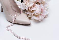 Vita kvinnors fartygskon, rosa pärlahalsband, steg vanlig hortensiablomman royaltyfri foto