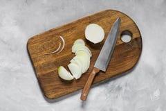 Vita lökar klippte med en kniv på ett träbräde royaltyfri bild