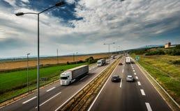 Vita lastbilar som passerar - huvudvägtrafik royaltyfri bild