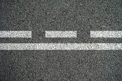 Vita linjer och rusade linjer på asfaltvägen Royaltyfri Fotografi