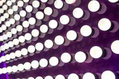 Vita ljus på purpurfärgad bakgrund Arkivbild