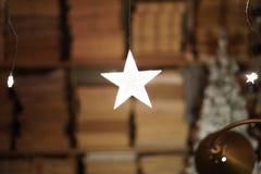 Vita ljusa stjärnor som hänger, bokhyllor i bakgrunden royaltyfria bilder