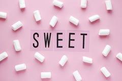 Vita marshmallower och SÖTT ord på rosa pastellfärgad bakgrund arkivfoton