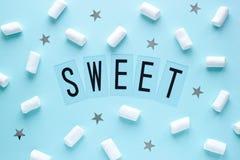 Vita marshmallower och stjärnor med SÖTT ord på blå pastellfärgad bakgrund fotografering för bildbyråer
