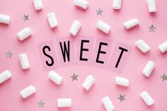 Vita marshmallower och stjärnor med SÖTT ord på rosa pastellfärgad bakgrund royaltyfria foton