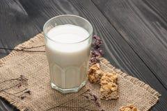 vita mejeriisoleringsprodukter Ett exponeringsglas av mjölkar serve med mandelgodisar på ett r royaltyfria foton