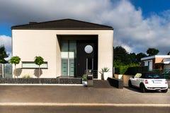 Vita Mini Cooper och ett härligt modernt hus arkivbild