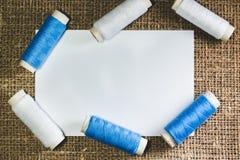 Vita modell och rullar av blåa och vita bomullstrådar på bakgrunden av ett ljust - brunt mattingtyg arkivbilder