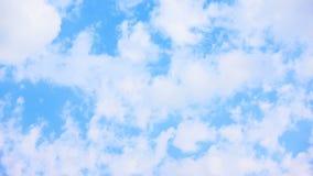 Vita moln som flyttar sig över blekt - blå himmel arkivfilmer