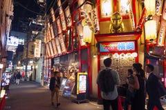 Vita notturna sulla via di Osaka City con i negozi, le barre ed i ristoranti decorati con le insegne al neon alla notte Fotografia Stock