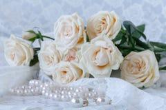 Vita nya blommor med pärlasmycken på den vita trätabellen Arkivfoton