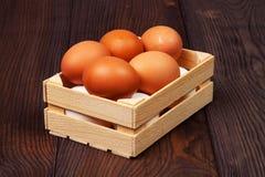 Vita och bruna ägg i träspjällåda på träbakgrund royaltyfri bild