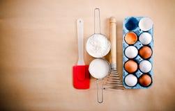 Vita och bruna ägg, morrhår och koppar med mjöl och socker Royaltyfria Bilder