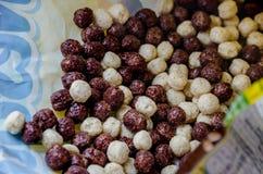 Vita och chokladbollar för frukost arkivfoton